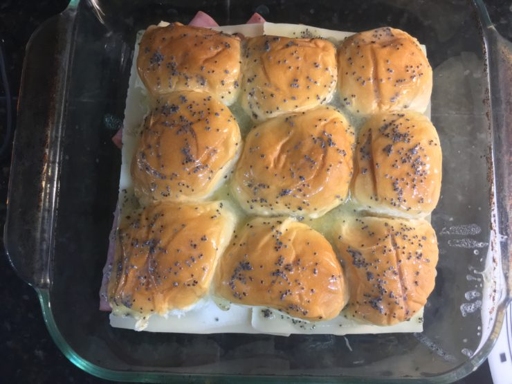 Nine Hawaiian Ham and Swiss Sliders are in a clear, glass 8x8 casserole dish and have been brushed with melted butter and poppy seeds. They are now ready to be baked in the oven.