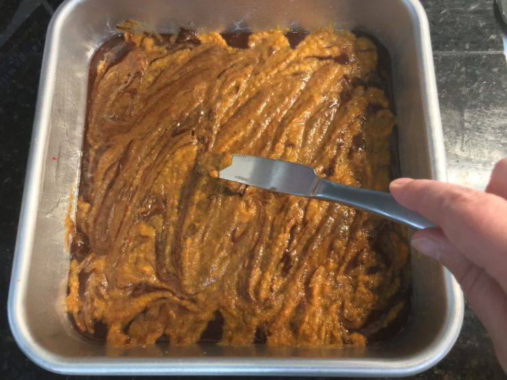 An 8x8 square cake pan with brownie mix in the pan. The pumpkin swirl mixture has been spread on top of the brownie mix in the pan. A butter knife is swirling the pumpkin mixture into the brownie mixture.