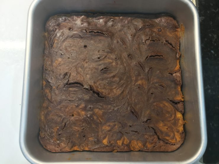 This is a silver, 8x8 square cake pan with baked Pumpkin Swirl Brownies in it.