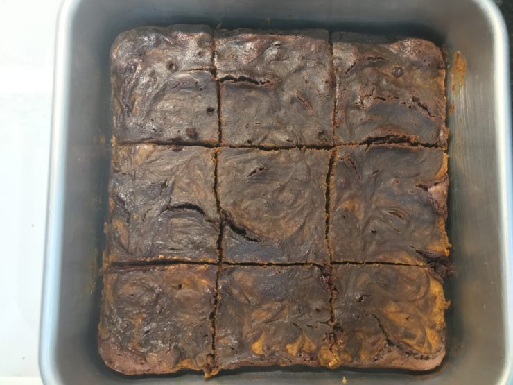 A silver, 8x8 square cake pan with baked Pumpkin Swirl Brownies in it. The Pumpkin Swirl Brownies have been cut into nine squares.