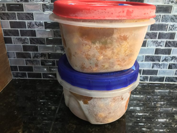 Two freezer safe, airtight containers of frozen Slow Cooker Vegetable Beef Soup sitting on a black granite counter top against a black and gray back splash.