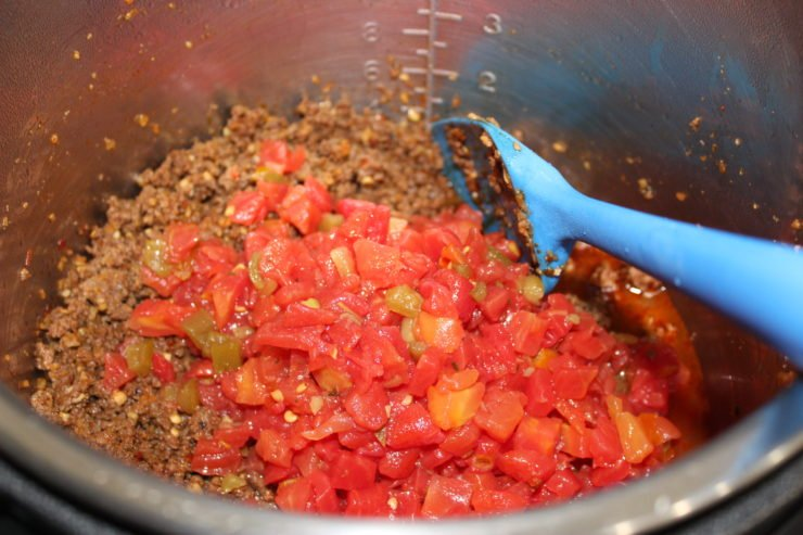 A silver, stainless steel Instant Pot Pressure Cooker insert that has cooked and crumbled, as well as seasoned, ground beef in it. Steam is coming off of the ground beef and a blue spatula is resting in the Instant Pot on the right hand side. Two cans of diced tomatoes with green chilies have been poured into the Instant Pot along with the juice.