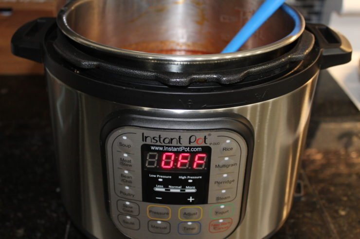"The lid has been removed from the Instant Pot and the red contents of the chili is revealed. The ground beef, kidney beans, tomatoes, and spices are just visible and the chili has been stirred. A blue spatula is resting in the Instant Pot on the right hand side. The silver front of the Instant Pot Duo is visible and the screen on the Instant Pot reads ""Off"". The Instant Pot is sitting on a black granite counter top with a blue, black, and gray tile back splash behind it."