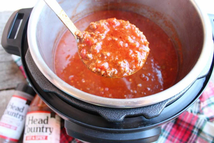 A weathered wood back drop with a red, white, green, and black tartan plaid fabric is the backdrop for this photo. A black and silver Instant Pot Pressure Cooker with Instant Pot Spicy Chili is on the right hand side of the photo, slightly out of frame. A silver and black ladle is holding a ladle full of chili out of the Instant Pot and a white hand is just visible coming out of the left hand side of the frame. A bottle of Head Country Hot and Spicy Bar-B-Q sauce is on the left hand side of the Instant Pot and a bottle of Head Country Bar-B-Q High Plains Heat championship seasoning is beside the bottle of bar-b-q on the left hand side.
