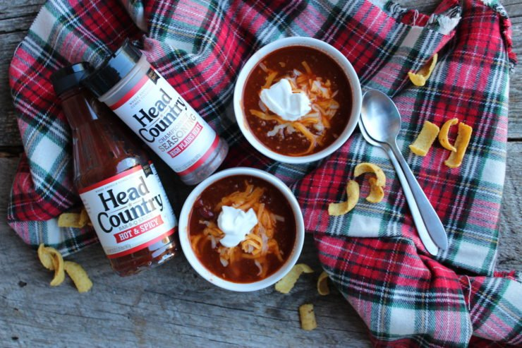 A wood board backdrop with a red, white, black, and green plaid tartan fabric with two white bowls filled with Instant Pot Spicy Chili sitting on the plaid. The chili is topped with a small dollop of white sour cream and some American and Colby shredded cheese. Corn chips are scattered on the board and the plaid, around the bowls of chili. Two brushed nickel silver teaspoons are placed on top of each other to the right hand side of the bowls of chili. One bottle of Head Country Hot and Spicy Bar-B-Q sauce is on the left hand side of the bowls of chili, and a bottle of Head Country Championship Seasoning High Plains Heat is also placed to the left of the bowls of chili, by the Bar-B-Q sauce.