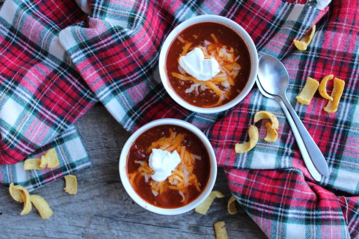 A wood board backdrop with a red, white, black, and green plaid tartan fabric with two white bowls filled with Instant Pot Spicy Chili sitting on the plaid. The chili is topped with a small dollop of white sour cream and some American and Colby shredded cheese. Corn chips are scattered on the board and the plaid, around the bowls of chili. Two brushed nickel silver teaspoons are placed on top of each other to the right hand side of the bowls of chili.