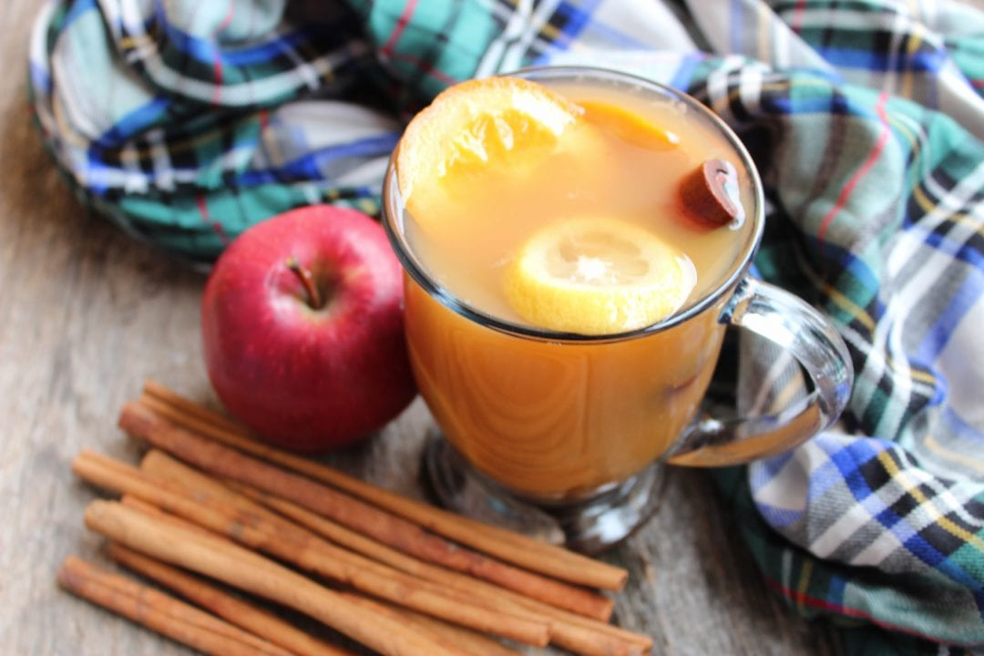 A clear, glass mug filled with Slow Cooker Spiced Apple Cider and topped with sliced orange, lemon, and a cinnamon stick. The glass is sitting on a wooden backdrop with cinnamon sticks and a whole, red apple in front of it. A green, red, black, white, and blue plaid cloth is wrapped around the mug on the right hand side.