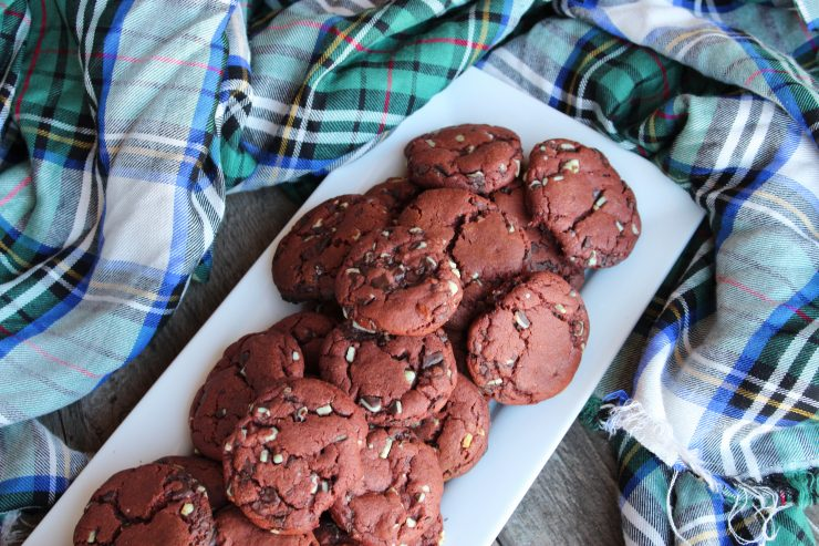 A long white platter filled with Chewy Chocolate Chip Peppermint Cookies sits on a wooden backdrop with a red, green, white, blue and black plaid cloth around it.