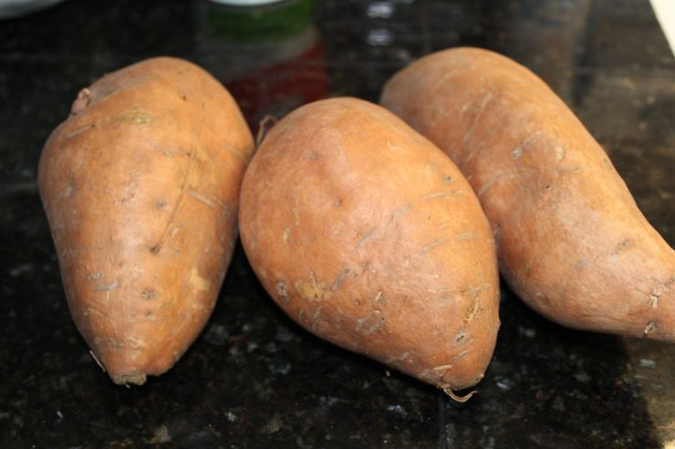 A black granite counter top with three large orange sweet potatoes on the counter.