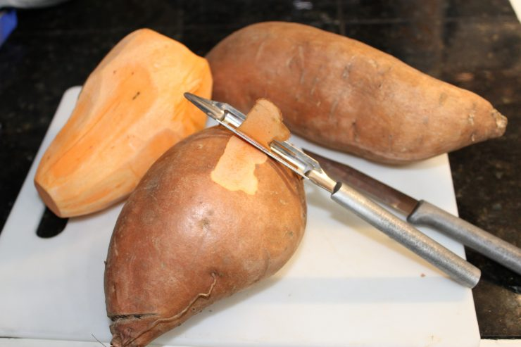 A white cutting board sits on a black granite counter top with three sweet potatoes on it. One potato is peeled, one is unpeeled, and one is in the process of being peeled with a silver potato peeler.