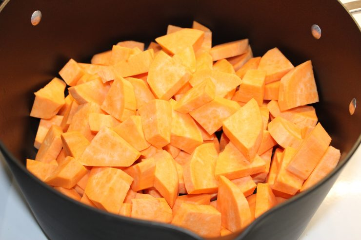 A large, black, pot holds peeled and diced sweet potatoes.