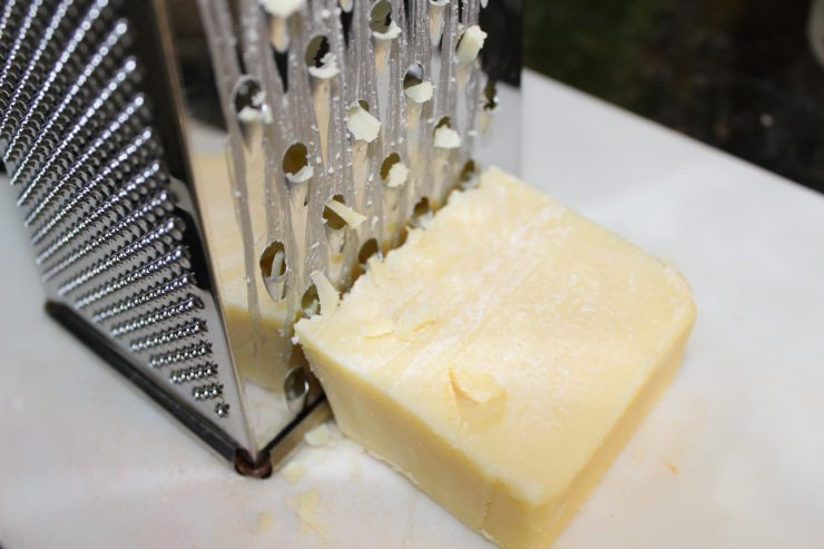 A silver cheese grater sits on a white cutting board with a small block of sharp, white cheddar cheese beside the grater.