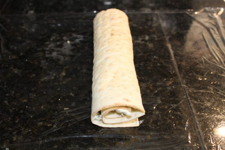 A flat bread filled with Cranberry Cream Cheese Pinwheel mix rolled like a burrito on a piece of plastic wrap. The plastic wrap is on a black, granite counter top.