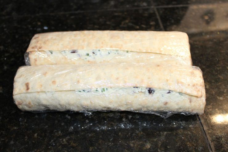 Two California Lavash flat breads filled with Cranberry Cream Cheese Pinwheel mix and rolled like burritos. Both rolled Lavash's are wrapped in plastic wrap and sitting on a black granite counter top.