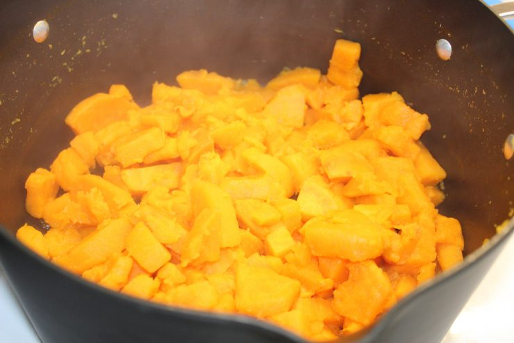 A large black pot sits on a white stove with steaming and cooked peeled and diced sweet potatoes. The water has been drained from the pot.