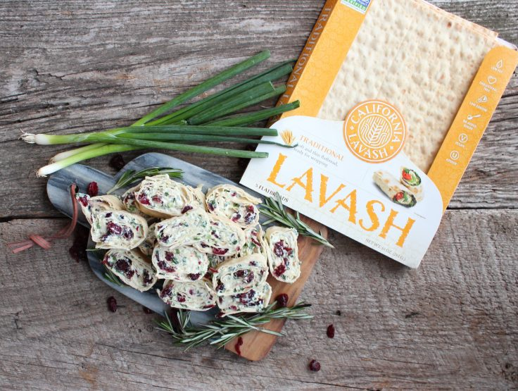 A overhead close up shot of a grey marble and wood cutting board, piled with Cranberry Cream Cheese Pinwheels and adorned with sprigs of rosemary and dried cranberries. Everything is on a wooden backdrop. A package of California Lavash flatbread is placed in the upper right corner of photo.