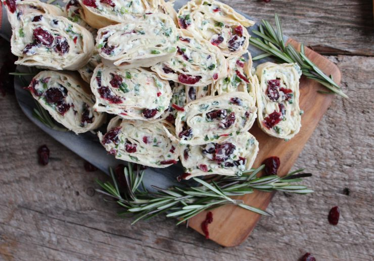 A overhead close up shot of a grey marble and wood cutting board, piled with Cranberry Cream Cheese Pinwheels and adorned with sprigs of rosemary and dried cranberries. Everything is on a wooden backdrop.
