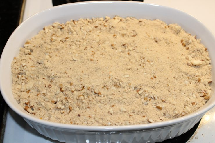 A white, oval casserole dish sitting on a white stove and filled with Sweet Potato Casserole, topped with a pecan streusel topping.