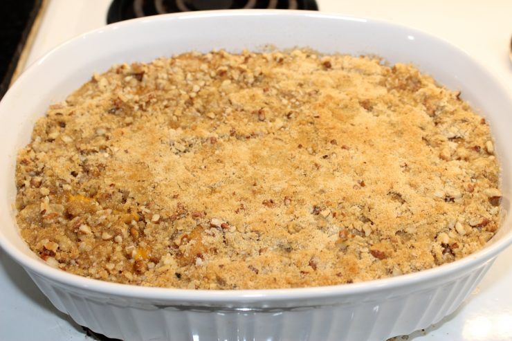 A baked Sweet Potato Casserole on a white stove top in a white oval casserole dish.