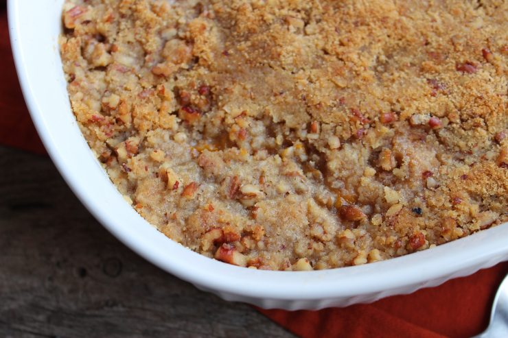 A close up of the Pecan Topped Sweet Potato Casserole in a white oval casserole dish sitting on a wood back drop.