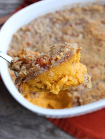 A white, oval casserole dish filled with Easy Sweet Potato Casserole and topped with Pecan Streusel topping. A orange towel is under the casserole dish and everything is sitting on a board back drop. A silver spoon is in the dish lifting some of the casserole out. A hand is just visible in the left hand corner lifting the spoon and some cinnamon sticks are placed on the left hand side of the casserole dish.