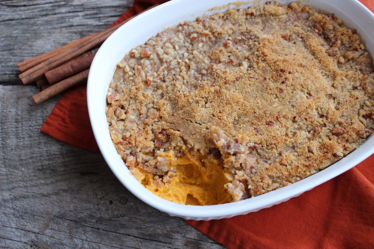 Easy Sweet Potato Casserole topped with Pecan Streusel in a white casserole dish. A spoon full of the casserole has been taken out of the right corner and the orange sweet potatoes under the topping are visible. Everything is sitting on a wood back drop and an orange towel is under the casserole dish. Some cinnamon sticks are placed on the left hand side of the casserole dish.