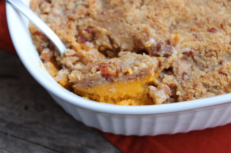 A white, oval casserole dish filled with Easy Sweet Potato Casserole and topped with Pecan Streusel topping. A orange towel is under the casserole dish and everything is sitting on a board back drop. A silver spoon is in the dish lifting some of the casserole out.