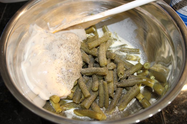 A silver mixing bowl with cooked and drained green beans, cream of mushroom soup, and milk inside. A white spoon is resting in the mixing bowl. Salt and pepper has been added to the ingredients in the mixing bowl.