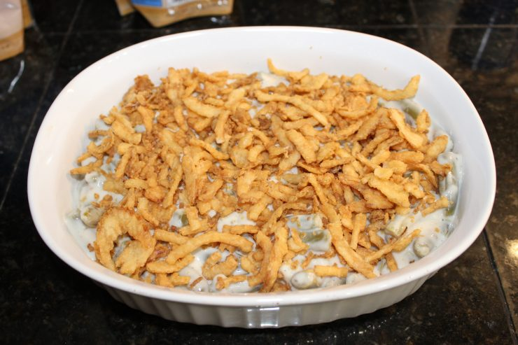 Skinny Green Been Casserole topped with French Fried onions in a white, oval casserole dish that is sitting on a black granite counter top.