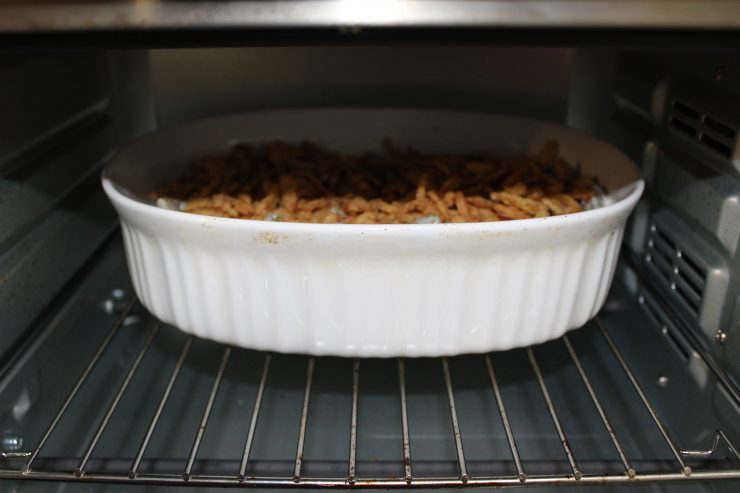 A white, oval, casserole dish filled with green bean casserole and topped with french fried onions in a silver oven.