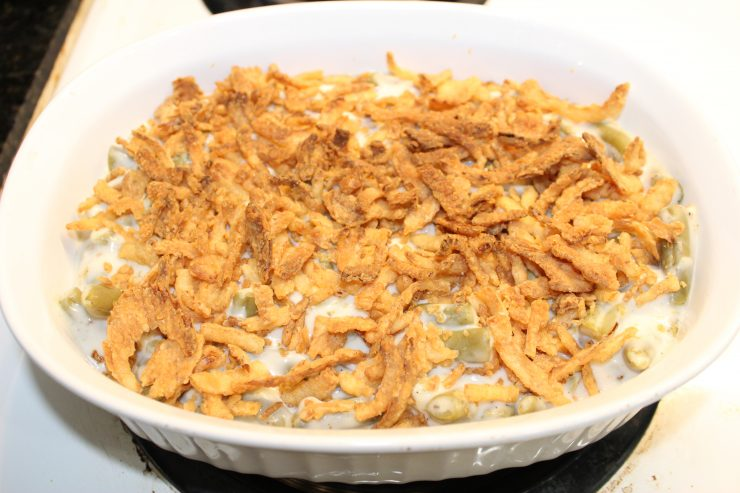A white, oval casserole dish filled with cooked Green Bean Casserole sitting on a white stove top.