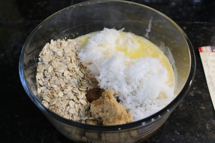 A small, glass mixing bowl with two beaten eggs, uncooked oatmeal, shredded coconut, brown sugar, vanilla, melted butter, and granulated white sugar in the bowl. The bowl is sitting on a black granite counter top with a hand written recipe to the right of the bowl.