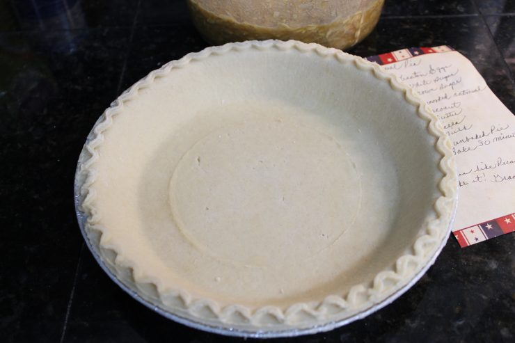 A frozen, unbaked deep dish pie crust sitting on a black granite counter top with a hand written recipe to the right hand side.