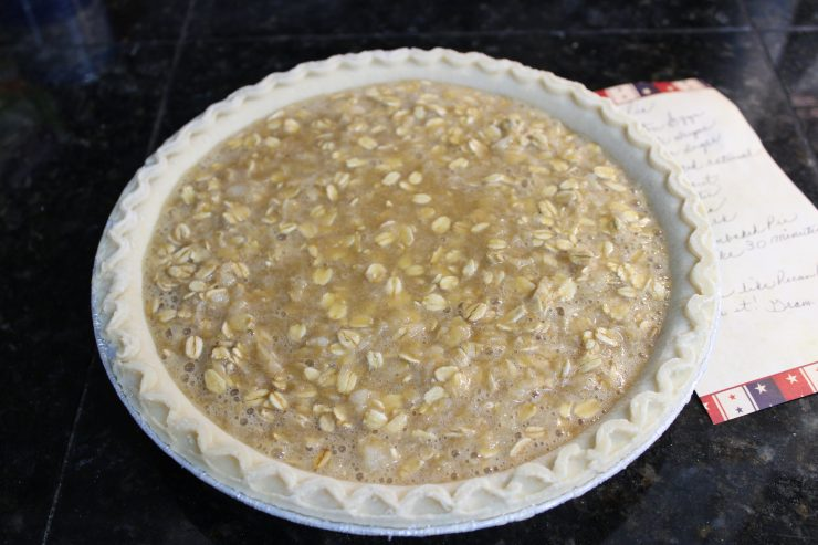 A frozen, unbaked deep dish pie crust sitting on a black granite counter top filled with Amish Oatmeal Pie with a handwritten recipe placed to the right side of it.