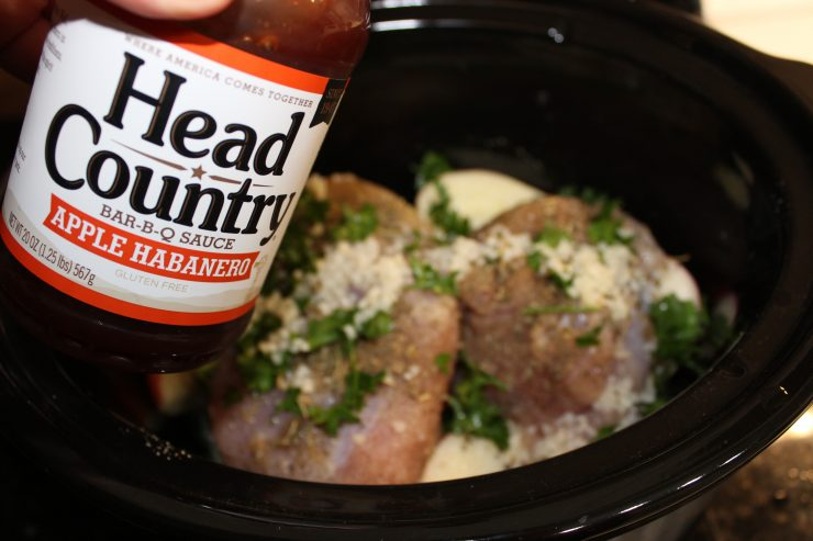 A bottle of the Best BBQ Sauce is coming in from the left hand side of the frame and being held over a black crock pot with herb seasoned turkey breast inside.