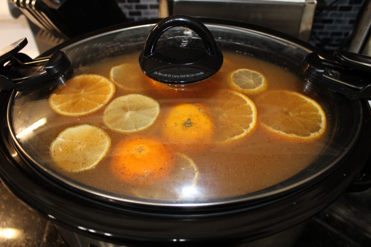 A large, black, oval slow cooker filled with apple cider, sliced oranges and lemons, cinnamon sticks and ground spices sitting on a black granite counter top. The clear glass lid has been placed on the slow cooker.