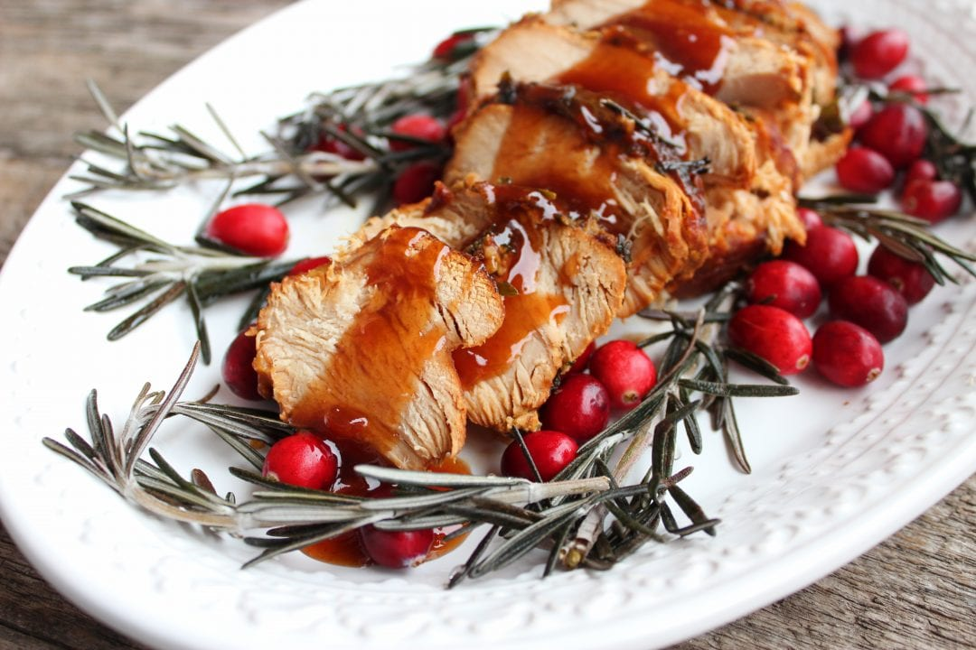 A white, oval platter with sliced turkey breast topped with Apple Habanero sauce down the center. Springs of fresh rosemary and fresh cranberries decorate the plate. The platter is sitting on a wooden backdrop.