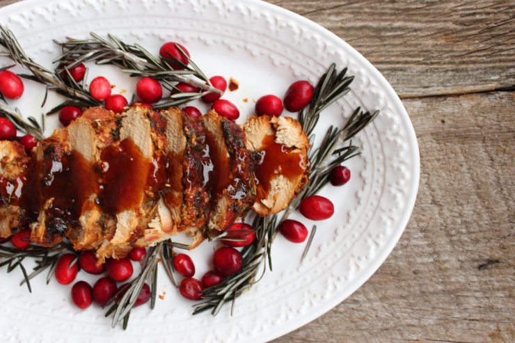 A white, oval platter coming in from the left hand side of the frame. The platter is sitting on a wooden backdrop and there is sliced turkey breast down the center of the platter. The turkey is topped with Apple Habanero sauce and sprigs of fresh rosemary and fresh cranberries are on the platter to the sides of the turkey breast.
