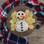 A Cheese ball shaped into a Snowman is sitting on a brown, wood round plate with wheat crackers surrounding it. A red, blue, white, and green plaid cloth is around the plate and everything is on a wooden backdrop.