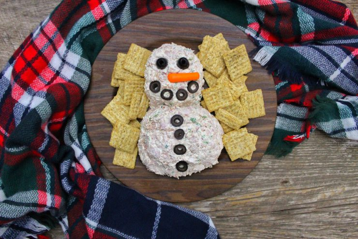 A Snowman Cheese ball is sitting on a round, wooden plate with olive eyes, mouth, and buttons, and a small, carrot stick nose. The cheese ball is surrounded by whole wheat crackers and a red, white, green, and blue plaid cloth is wrapped around the plate. Everything is siting on a wooden backdrop.
