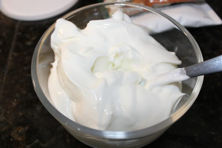 A small clear glass bowl containing plain, nonfat Greek yogurt is on a black counter top with a silver spoon resting inside the bowl.