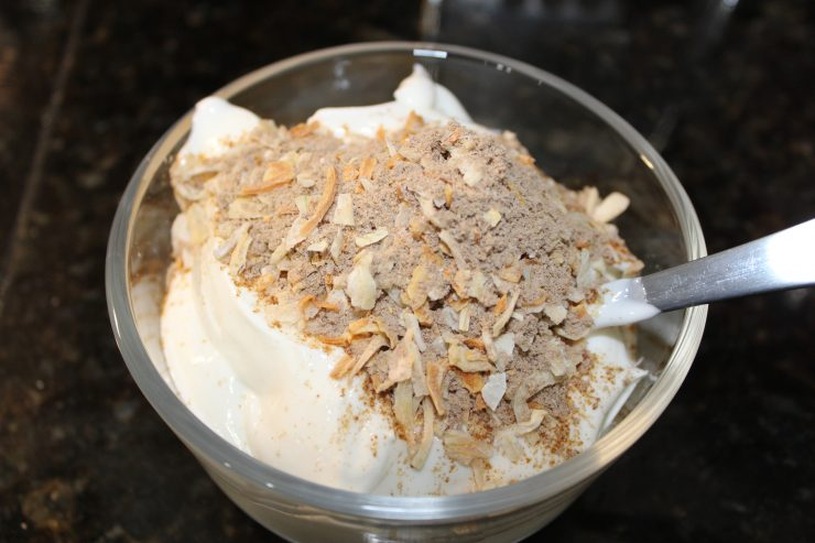 A small, clear, glass bowl sits on a black counter top with plain Greek yogurt inside and a packet of dry onion soup mix has been added to the top of the Greek yogurt in the bowl.