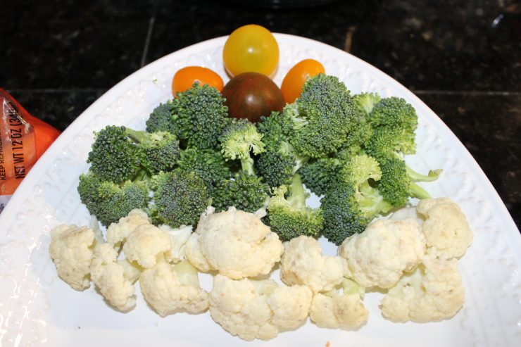 Four cherry tomatoes are arranged at the top of a white, oval platter with broccoli florets in a straight, horizontal line below them, followed by a horizontal line of cauliflower. The platter is sitting on a black, granite counter top.