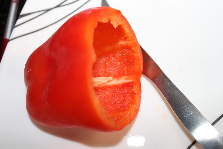 A red bell pepper sits on a white plate with the top stem area cut off. A silver paring knife rests beside the bell pepper.