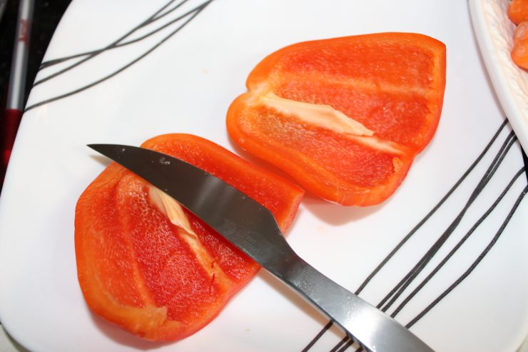 A red bell pepper is cut in half sitting on a white plate with a silver paring knife beside it. The center membrane and seeds have been removed from the bell pepper.