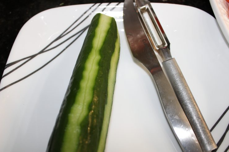 A long. green, English cucumber is sitting on a white plate and is partially peeled creating small strips of peeling around the cucumber. A silver paring knife and silver vegetable peeler is resting beside the cucumber.