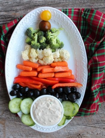 Yellow cherry tomatoes, broccoli florets, cauliflower florets, carrots sticks, red pepper sticks, black olives, and sliced cucumber with a bowl of French Onion Dip are arranged on an oval, white platter to create a Christmas Tree Veggie Tray. A red, green, and black tartan cloth is underneath the platter and everything is sitting on a wooden backdrop.