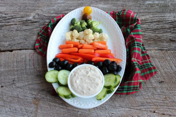 A white, oval platter is sitting on a wooden backdrop with vegetables arranged in a Christmas Tree on it. The stump of the tree is made with a white bowl containing French Onion Dip recipe. A red, green, and tartan cloth has been placed underneath the platter.