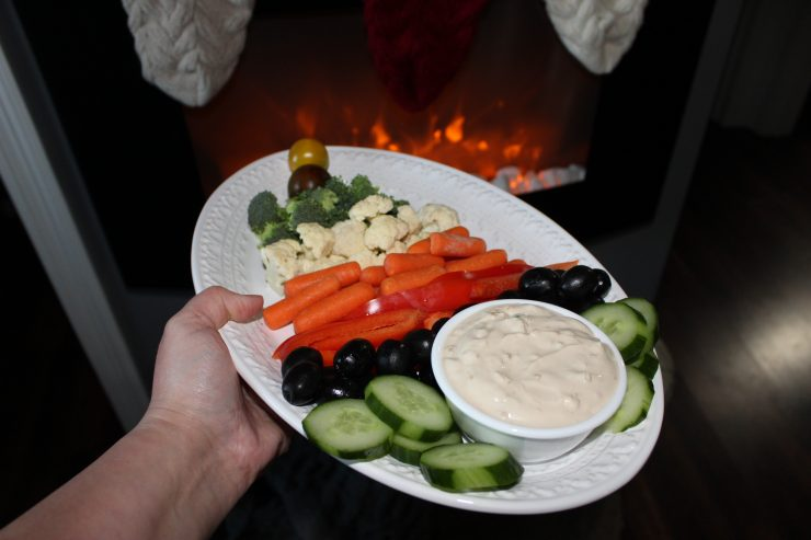 A hand and arm is coming out of the left hand side of the frame and is holding a white platter with a Christmas Tree made from vegetables and a bowl of French Onion Dip. The platter is being held in front of a fireplace.