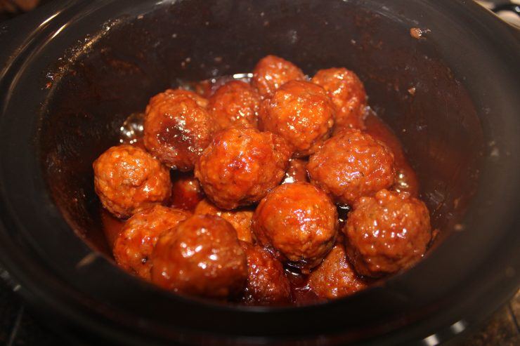 A small, black slow cooker filled with cooked, Slow Cooker Party Meatballs covered in the Best BBQ Sauce, grape jelly, water, and apple cider vinegar that has been mixed together to create a beautiful, red sauce.
